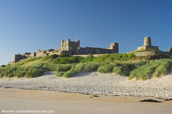 Early summer morning view of Bamburgh Beach and Castle.