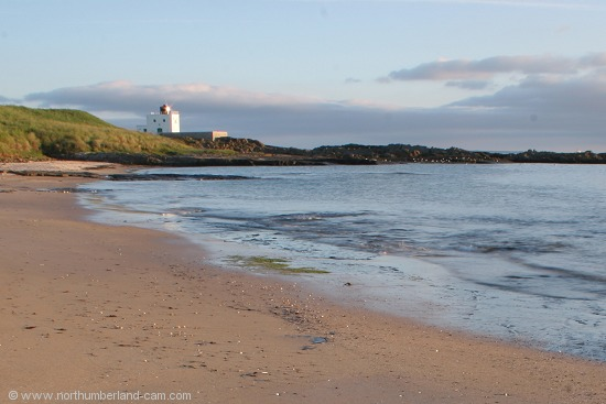 Early summer morning view of Bamburgh Beach and Lighthouse.