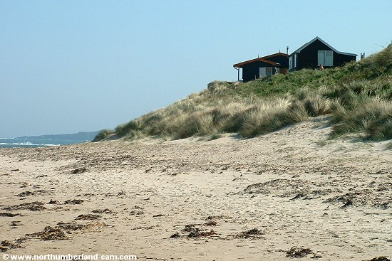View at the south end of the beach with holiday homes on the dunes above.
