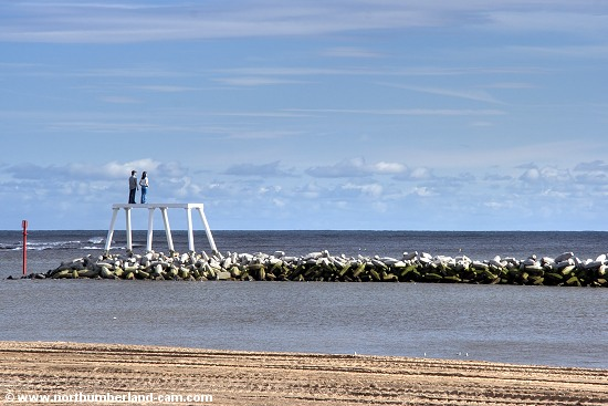 View from the beach to the breakwater and sculpture in the middle of the bay.
